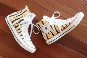 A pair of custom Converse high tops hand painted with black and gold Mizzou tiger stripes by artist Lauren Rundquist at LaQuist.