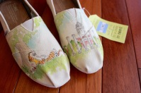 A custom pair of Mizzou and Calvin and Hobbes toms shoes hand painted by artist Lauren Rundquist at LaQuist.