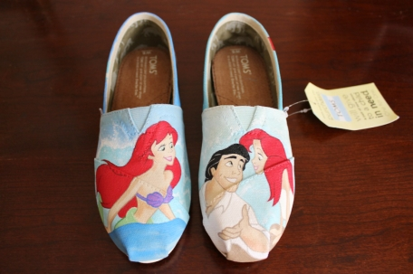A custom pair of Little Mermaid TOMS painted with Ariel, Prince Eric, Flounder, and Sebastian, by artist Lauren Rundquist at LaQuist.