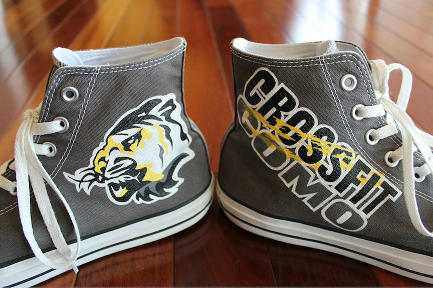 A custom pair of high top Converse painted for Crossfit CoMo, by artist Lauren Rundquist at LaQuist.