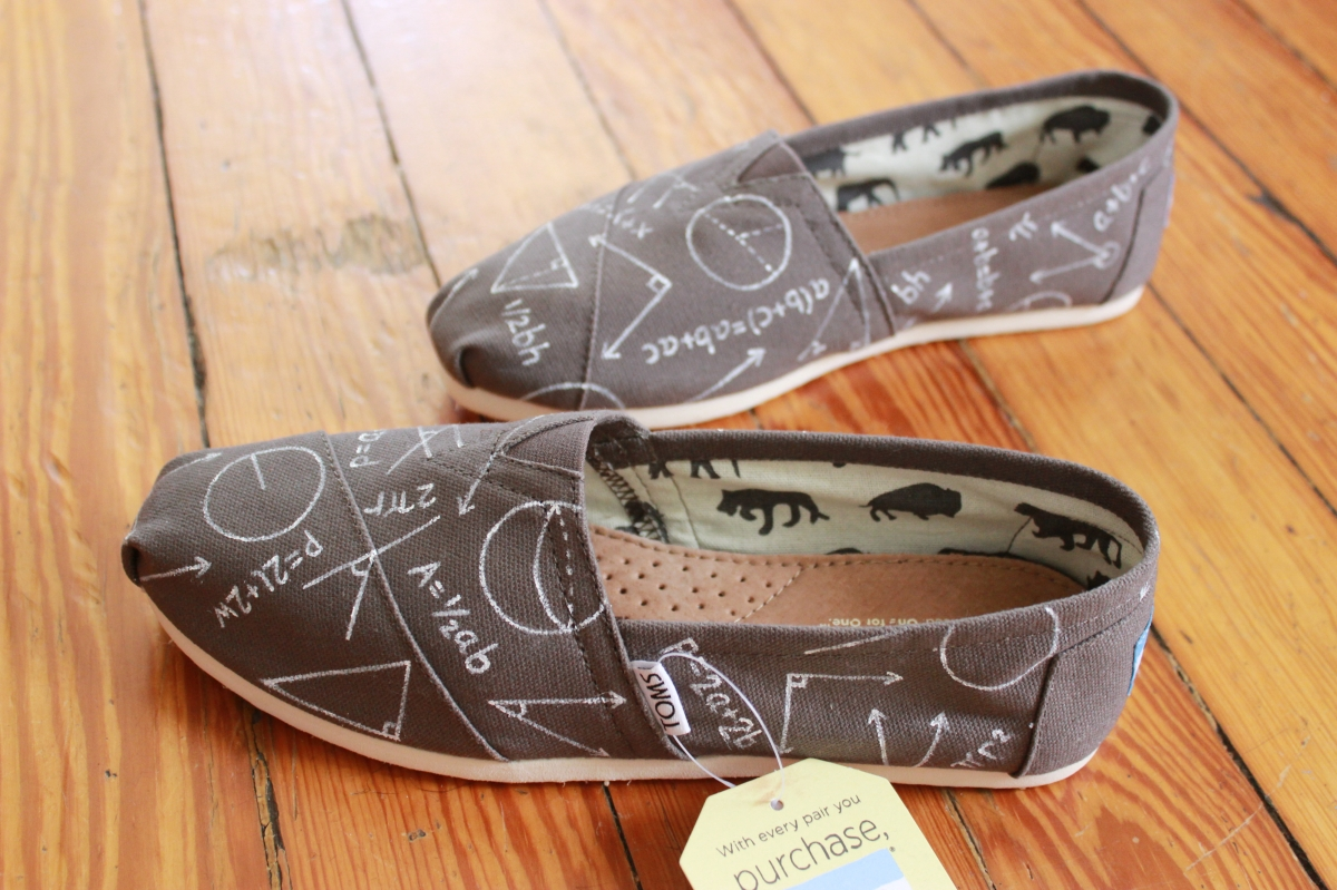 A pair of custom TOMS hand painted with geometry and algebra symbols by artist Lauren Rundquist at LaQuist.