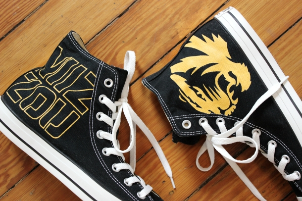 A custom pair Mizzou high top Converse with the football helmet logo by artist Lauren Rundquist at LaQuist.