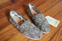 A hand painted pair of bicycle and flower TOMS shoes by artist Lauren Rundquist at LaQuist.