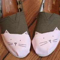 A hand painted pair of cat TOMS shoes with 'meow' written on the backs by artist Lauren Rundquist at LaQuist.