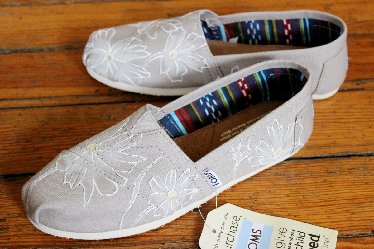 A hand painted pair of floral daisy TOMS shoes by artist Lauren Rundquist at LaQuist.