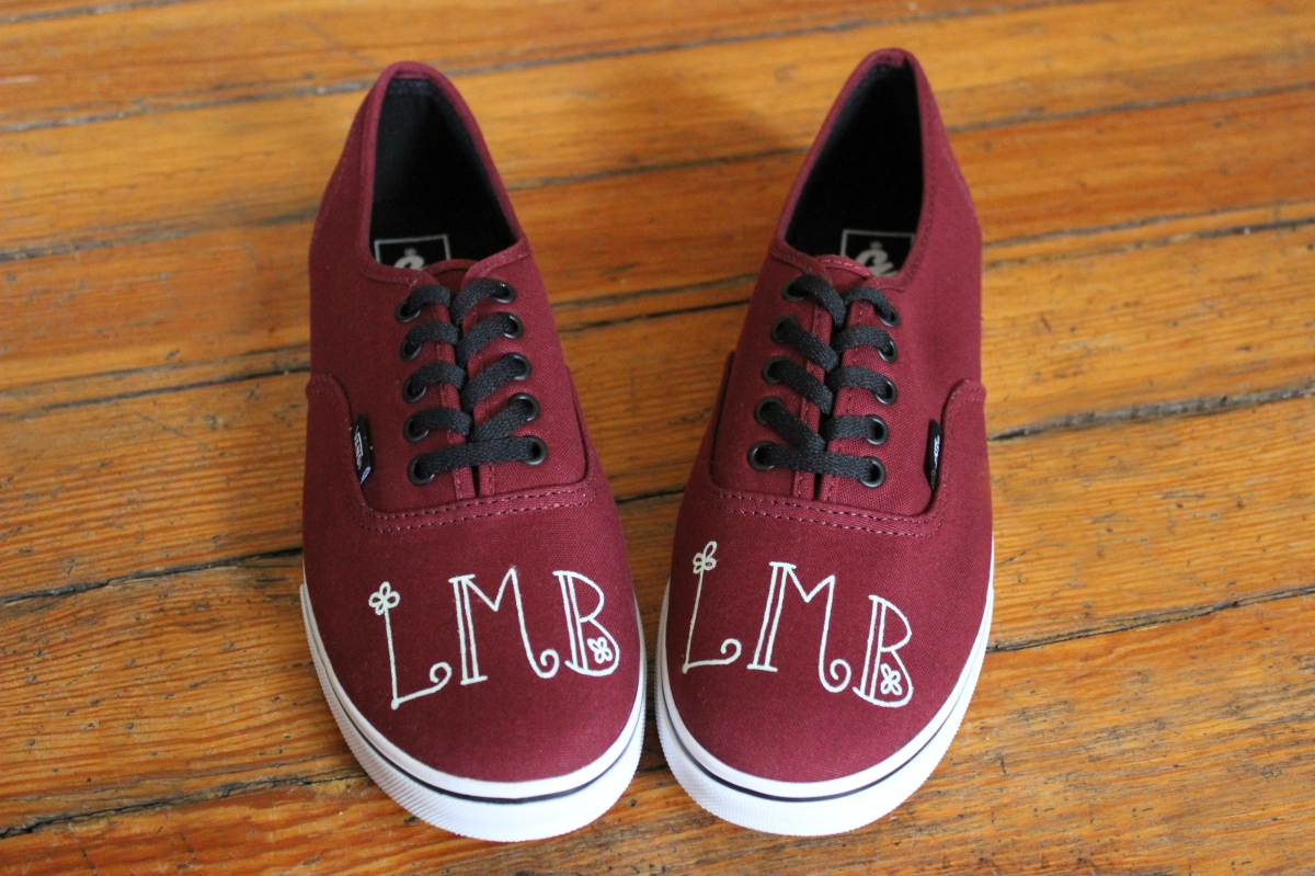 A hand painted pair of custom monogrammed Vans shoes by artist Lauren Rundquist at LaQuist.