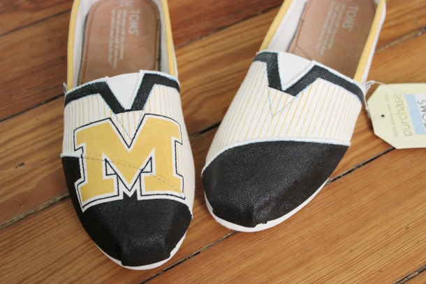 A hand-painted pair of custom Mizzou Tigers TOMS shoes by artist Lauren Rundquist at LaQuist.