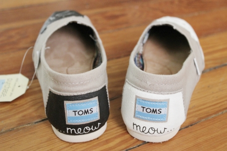 A custom pair of cat TOMS painted with 'meow' by artist Lauren Rundquist at LaQuist.