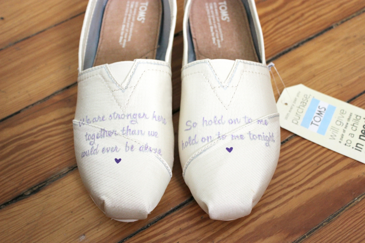 A hand-painted pair of custom bridal TOMS shoes painted with wedding song lyrics by artist Lauren Rundquist at LaQuist.