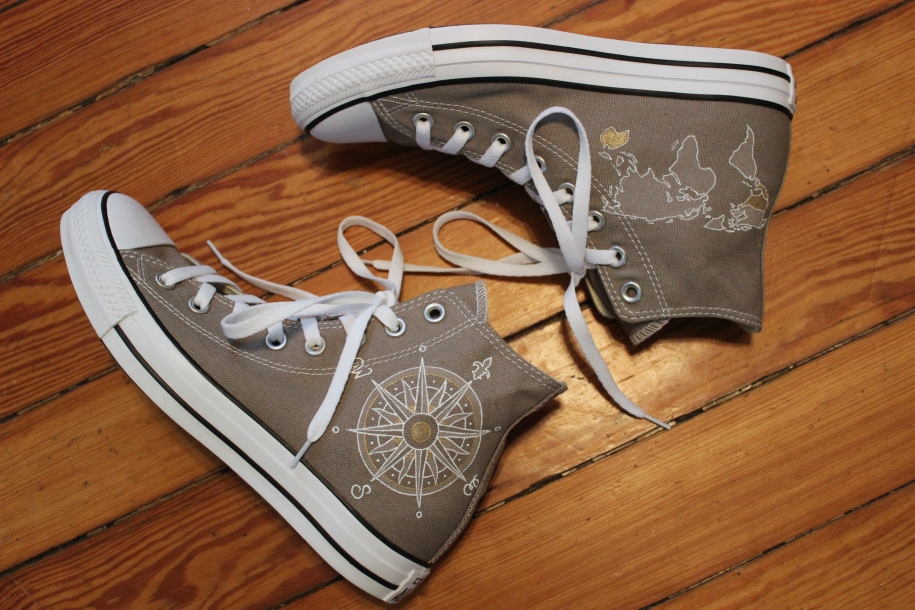 A hand painted pair of custom Converse high tops with a world map and compass by artist Lauren Rundquist at LaQuist.