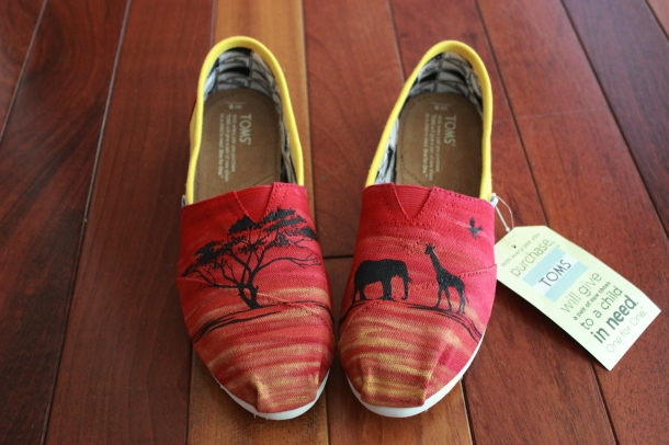 A pair of custom TOMS hand painted with a sunset and African animal and tree silhouettes by artist Lauren Rundquist at LaQuist.