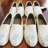 A hand painted pair of matching wedding party TOMS shoes by artist Lauren Rundquist at LaQuist.