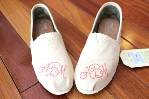 A hand painted pair of custom monogrammed TOMS shoes by artist Lauren Rundquist at LaQuist.