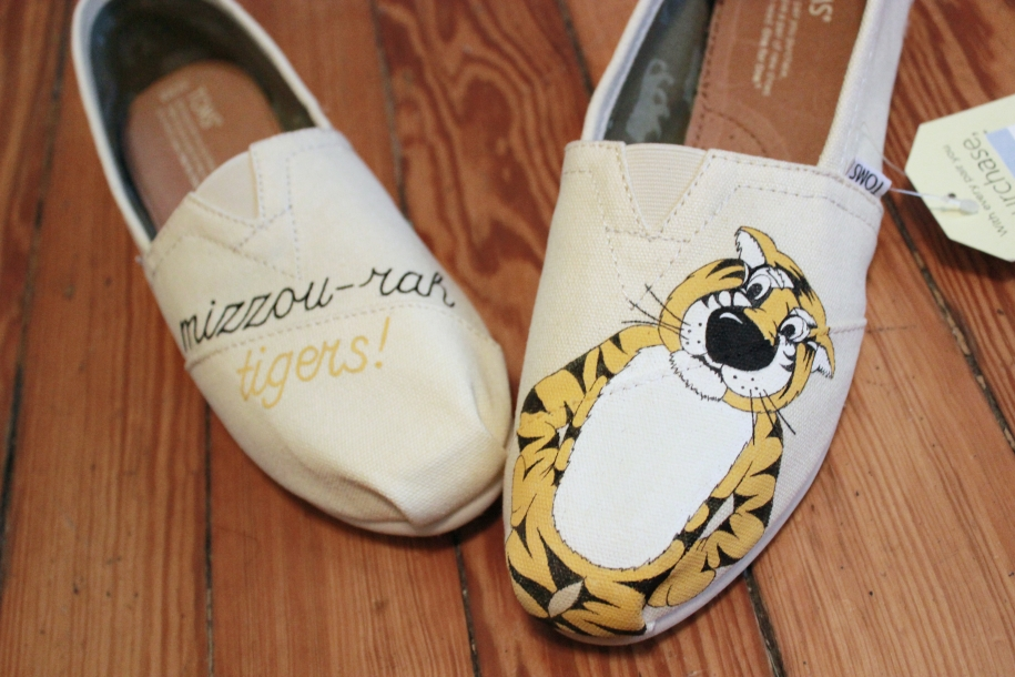A pair of custom TOMS hand painted with Truman the Tiger for Mizzou by artist Lauren Rundquist at LaQuist.