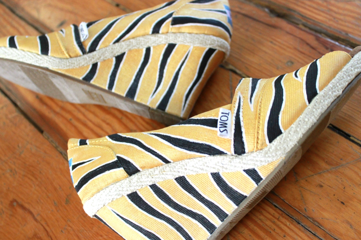 A pair of custom TOMS wedges hand painted with black and gold Mizzou tiger stripes by artist Lauren Rundquist at LaQuist.