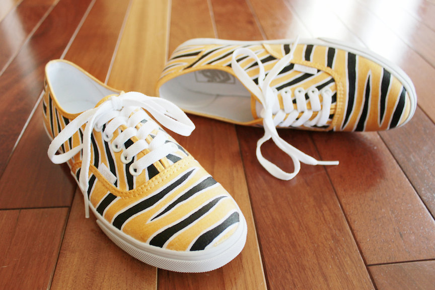A pair of custom Vans hand painted with black and metallic gold Mizzou tiger stripes by artist Lauren Rundquist at LaQuist.