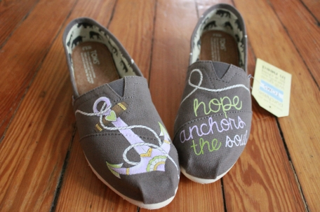 "A hand painted pair of nautical anchor TOMS shoes with the quote ""Hope anchors the soul"" by artist Lauren Rundquist at LaQuist."