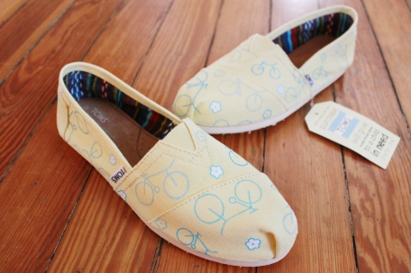 A pair of custom TOMS hand painted with bicycles and flowers by artist Lauren Rundquist at LaQuist.