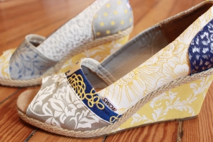 A pair of custom bridal TOMS wedges hand painted with a variety of patterns by artist Lauren Rundquist at LaQuist.