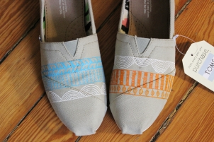 A pair of custom Solea Water TOMS hand painted by artist Lauren Rundquist at LaQuist.