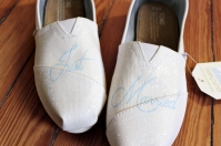 A pair of custom glitter wedding TOMS hand painted by artist Lauren Rundquist at LaQuist.