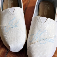 A pair of custom glitter wedding TOMS hand painted by artist Lauren Rundquist at LaQuist.