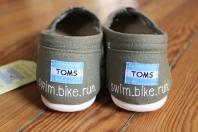 A pair of custom triathlon swim, bike, run TOMS hand painted by artist Lauren Rundquist at LaQuist.
