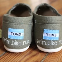 A pair of custom triathlon swim, bike, run TOMS hand painted by artist Lauren Rundquist at LaQuist.