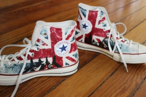 A pair of UK British flag high top Converse shoes hand painted with the Beatles at Abbey Road and the London skyline by artist Lauren Rundquist at LaQuist.