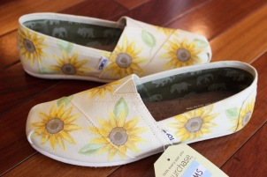 A pair of sunflower TOMS shoes hand painted by artist Lauren Rundquist at LaQuist.