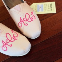 A pair of monogram initials TOMS shoes hand painted by artist Lauren Rundquist at LaQuist.
