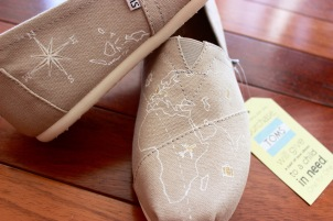 A pair of custom world map TOMS hand painted by artist Lauren Rundquist at LaQuist.